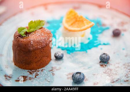 Chocolate fondant dessert pudding with blue ice cream on plate with orange. - Stock Photo