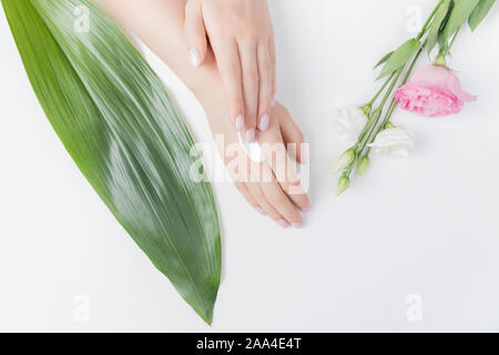 Girl puts cream on hands on white background with tropical leaves and pink flowers, top view. Concept of skin care, anti-aging frost. - Stock Photo