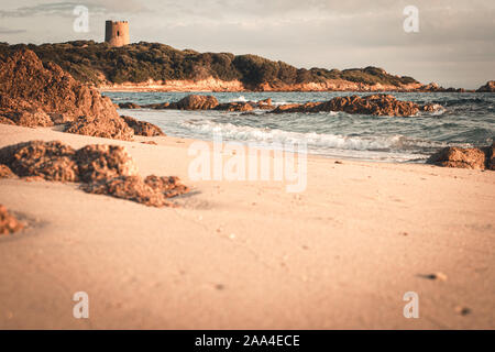 Amazing beach at sunrise with Genoese tower in the background, Vignola Mare - Stock Photo