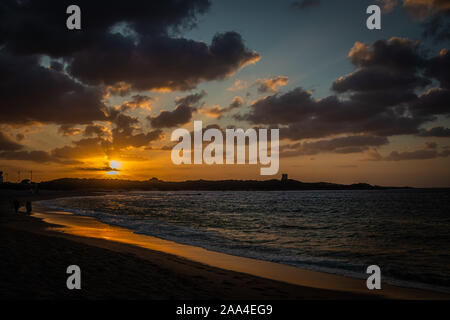 Amazing colors of sunset at the beach in Vignola Mare - focus is on the horizon - Stock Photo