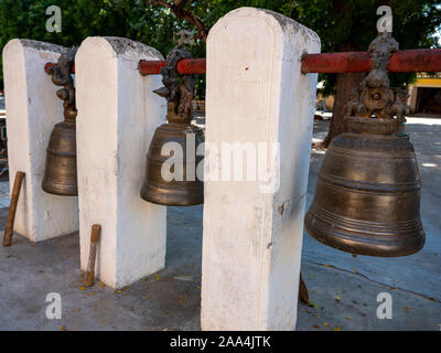 Three large hanging temple bells with mallets of the Shwezigon Pagoda in Bagan, Myanmar (Burma) used to call monks to prayer or ward off evil - Stock Photo
