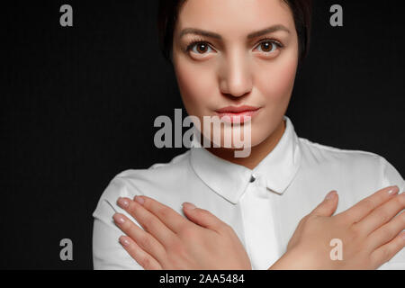 portrait of Asian brunette woman in white shirt with arms crossed on chest on black background