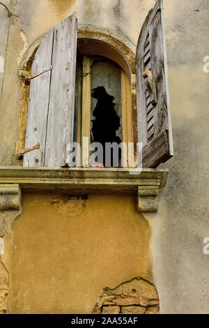 Old, derelict window with broken wooden shutters and glass in old building Croatia - Stock Photo