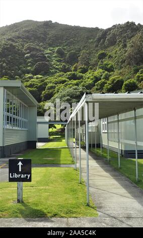 Outside library signage amidst old school buildings - Stock Photo