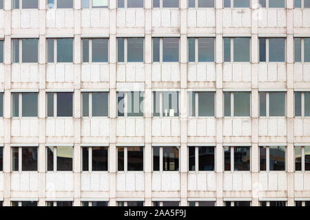 Gray facade of a multi storey office building with a symmetrical pattern of windows. - Stock Photo