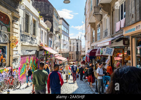 Tourists walk downhill past shops and cafes on a busy summer day in the Galata Karakoy district of Istanbul, Turkey - Stock Photo