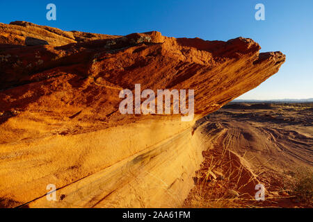 Sandstone Cliffs that have been undercut from erosion hang precariously above the desert floor in the area around Lake Powell. - Stock Photo