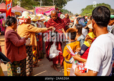 Monks Walk Down The Main Street In Pindaya Seeking Alms During The Pindaya Cave Festival, Pindaya, Shan State, Myanmar. - Stock Photo