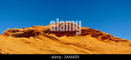 The shapes and undulations of a sandstone cliff almost looks like a wave just breaking. - Stock Photo