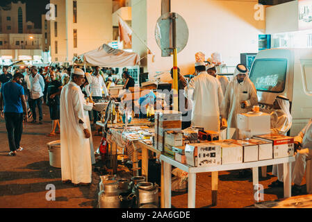 Men in traditional thobes sell and buy goods from street stalls in Souq Al-Haraj, Doha, Qatar - Stock Photo