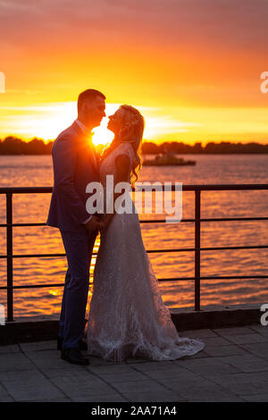 Young beautiful couple of newlyweds with bride and groom walk on the terrace by the ocean during a wedding ceremony in a wedding dress and suit kissin - Stock Photo
