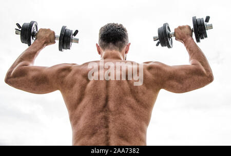Pain is temporary, pride is forever. Muscular man exercising with dumbbell rear view. Sportsman with strong back and arms. Sport equipment. Bodybuilding sport. Sport lifestyle. Dumbbell exercise gym. - Stock Photo