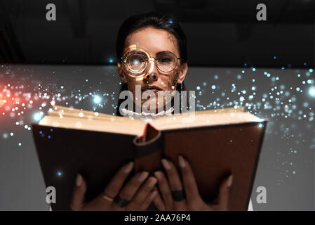 low angle view of steampunk woman in glasses reading book with glowing illustration above - Stock Photo