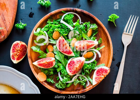 Autumn salad of arugula, figs in brown earthenware plate on a dark background. top view - Stock Photo