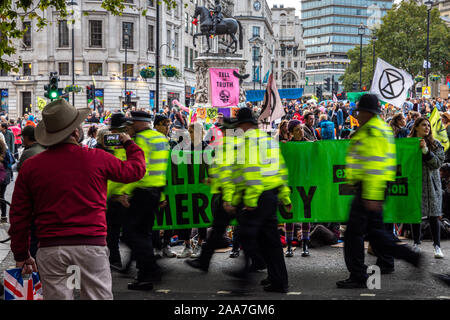 London, England, UK - October 10, 2019: A tourist takes a photograph of an Extinction Rebellion protest in Trafalgar Square in central London. - Stock Photo