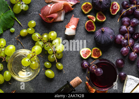 Buffet with wine snack set or appetizer. Italian meat, glasses of wines, cheese, grapes and figs. - Stock Photo