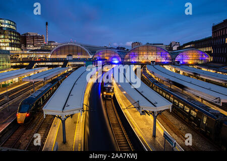 London, England, UK - September 22, 2019: Passenger trains stand at the platforms of London's Paddington Station at dusk. - Stock Photo