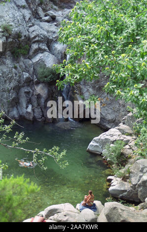 Gorges d'Héric, Monts de l'Espinouse, Hérault, Occitanie, France: swimming and sunbathing by a rock pool (Gouffre du Cerisier) in the mountains.  MODEL RELEASED - Stock Photo