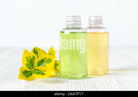 bottles of natural shower gel and shampoo with plants - Stock Photo