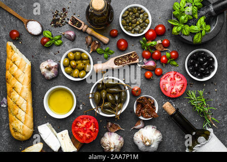 Italian food or mediterranean diet background: herbs, olive, oil, tomato, bread, cheese and wine bottle