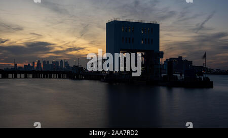 London, England, UK - September 21, 2019: The sun sets behind Woolwich's ferry pier, with the skyline of London's Docklands in the distance. - Stock Photo