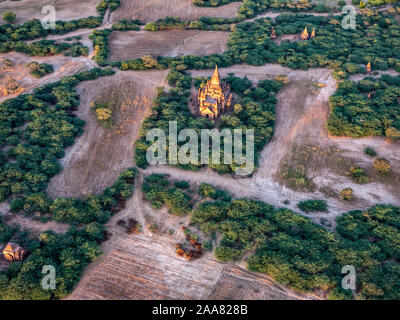 Aerial view of the ancient temples of the archeological zone of Bagan, Myanmar (Burma) as seen from a hot air balloon flying overhead at dawn - Stock Photo