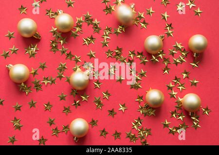 Golden balls and stars glitter confetti on red background. Party holiday backdrop. View from above, flat lay style. - Stock Photo