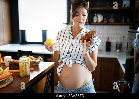 Young pregnant woman with apple and bread in her hands in kitchen. Concept of healthy food. - Stock Photo