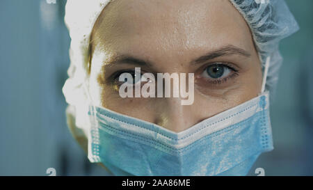 Extra close-up of the surgeon's eye. She is tired, after surgery, looking into the camera - Stock Photo