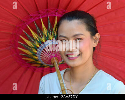 Young Thai woman poses for the camera under a traditional oil-paper parasol. - Stock Photo