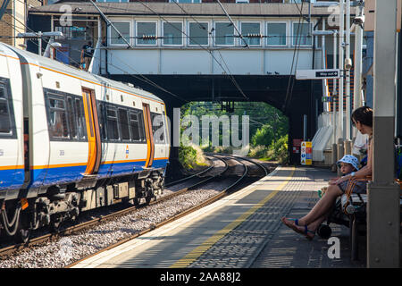 London, England, UK - July 24, 2019: Passengers wait for a train at Kensal Rise Station on a sunny summer day on the London Overground. - Stock Photo