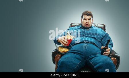 Portrait of fat caucasian man wearing jeanse and whirt sitting in a brown armchair on gradient grey background. Watching TV drinks beer, eats chips, fried potato. Overweight, carefree.