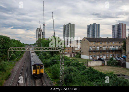 London, England, UK - June 1, 2019: A Greater Anglia commuter train passes council housing of the Alma Estate at Ponder's End in the North London subu - Stock Photo