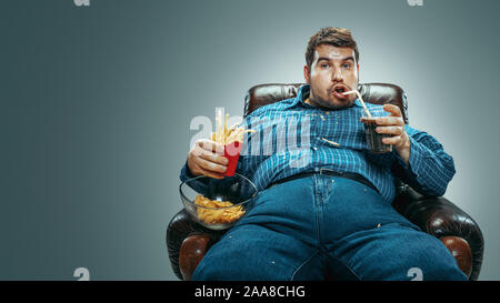 Portrait of fat caucasian man wearing jeanse and whirt sitting in a brown armchair on gradient grey background. Watching TV drinks cola, eats chips, fried potato, laughting. Overweight, carefree.