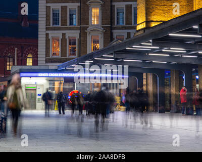 London, England, UK - November 22, 2018: Crowds of commuters walk through King's Cross railway station in London on a winter evening. - Stock Photo