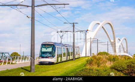 A Citadis streetcar of Strasbourg tramway has crossed the Beatus Rhenanus bridge coming from Kehl in Germany on the other side of the Rhine. - Stock Photo