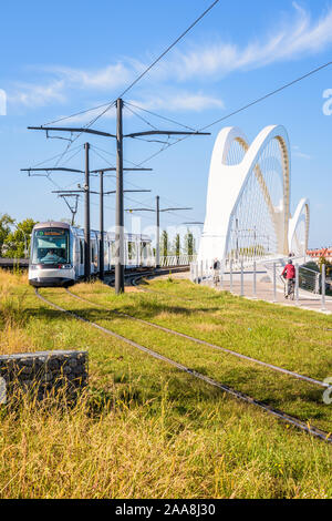 A Citadis streetcar of Strasbourg tramway has crossed the Beatus Rhenanus bridge coming from Strasbourg in France on the other side of the Rhine. - Stock Photo