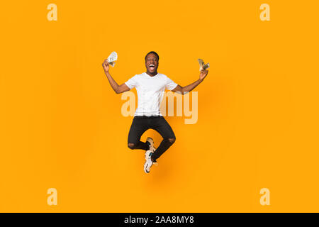 Excited Afro Man Holding Money Jumping In Air, Orange Background - Stock Photo
