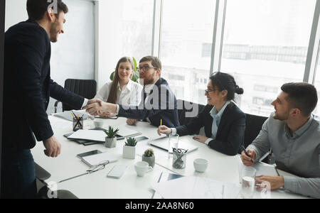 Satisfied HR managers shaking hands with applicant - Stock Photo