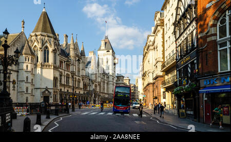 London, England, UK - July 8, 2013: A double-decker bus stops at a pedestrian crossing outside the Royal Courts of Justice on London's Fleet Street. - Stock Photo