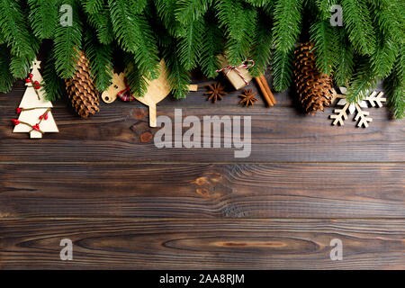 Top view of frame made of fir tree branches and holiday decorations on wooden background. Christmas concept with empty space for your design. - Stock Photo