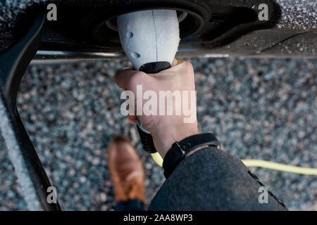 mans hand holding electric car plug - Stock Photo