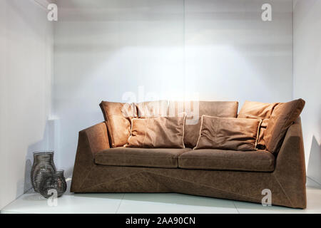 Brown leather sofa in a bright room. Real photo - Stock Photo