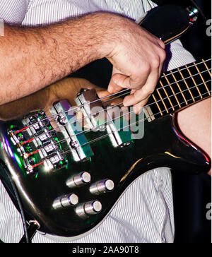 close-up of a male bass guitarist for the band 'Backstreetsoundsystem' plucks the strings with dexterity. On a black background - Stock Photo