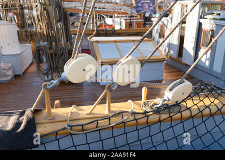 Old vintage pulley system with rigging ropes on a tall ship in a close up view. - Stock Photo