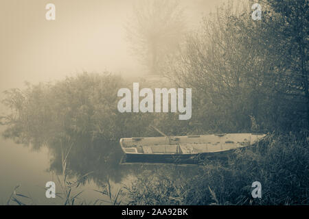Old row boat at the waterfront in a misty frozen scenery early in the morning, picture taken at lake Kotermeerstal the Netherlands, province Overijsse - Stock Photo