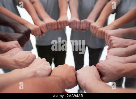 group of young people making a circle out of their hands - Stock Photo