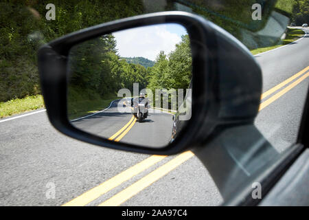 looking at side view mirror at motorcyclist parkway us 441 highway route through great smoky mountains national park usa - Stock Photo