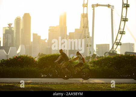 (Selective focus) People cycling in a public park with the skyline of Singapore in the background. - Stock Photo