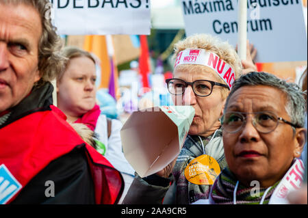 A female hospital worker shouting slogans through a paper megaphone during the demonstration.Four trade unions, FNV, FBZ, NU'91 and CNV launched the national campaign to strike over ongoing negotiations with the Dutch Association of Hospitals (NVZ). Thousands of hospital workers gathered at the Jaarbeursplein where Chairman Ad Melkert of the Dutch Association of Hospitals (NVZ) received 37.457 signatures demanding a five percent structural wage increase and extra allowance on wages when employees are called to work last-minute. They also demand agreements concerning heavy staff workloads, as w - Stock Photo